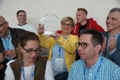 Widownia, prezes PKOIA, Małgorzata Pietrzak prezentuje pamiątkę za udział we wszystkich edycjach Mistrzostw.