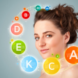 Pretty young girl with colorful vitamin icons and symbols on gradient background